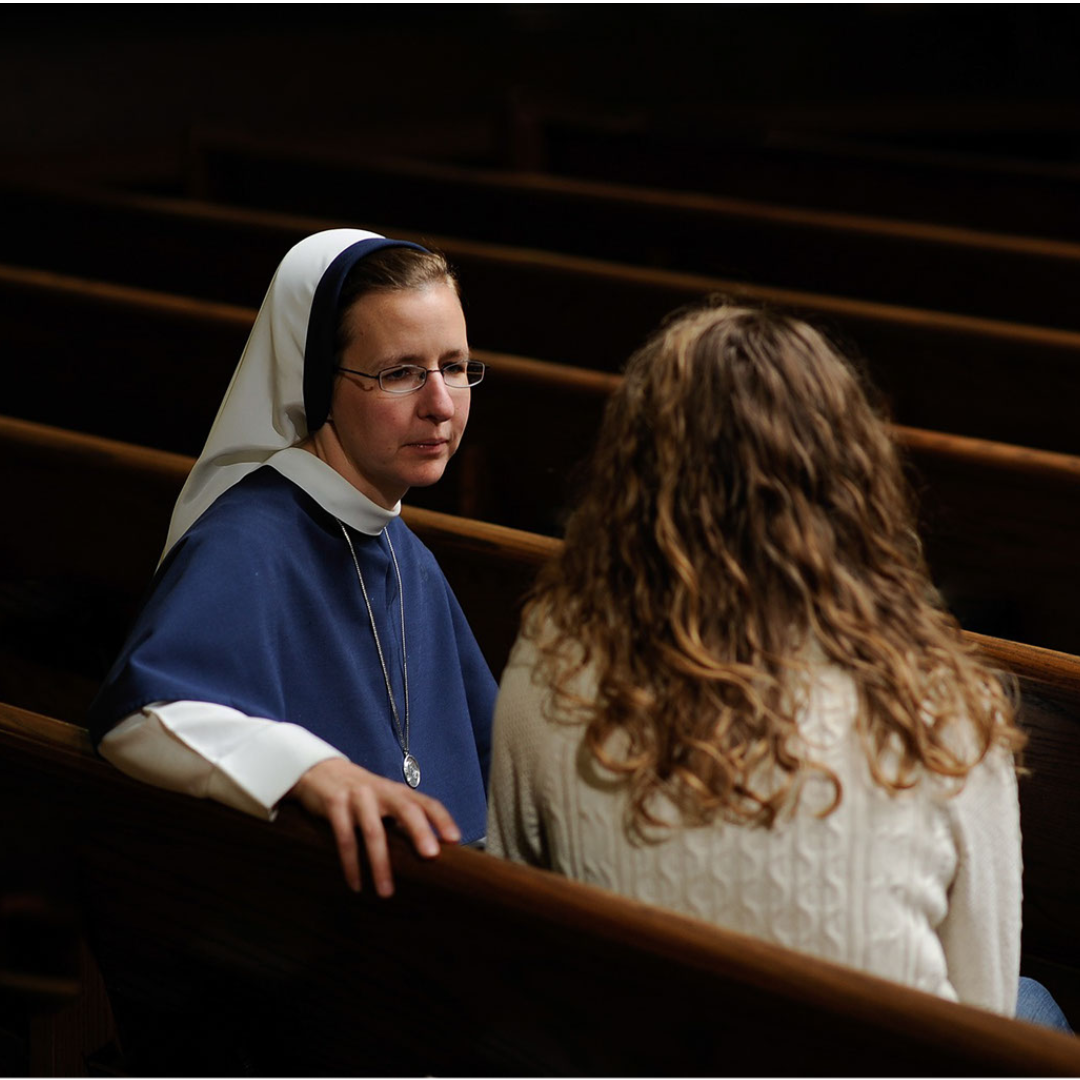 Religious sister talking with a young woman in church